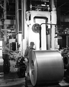 Black & white photo of workers rolling steel