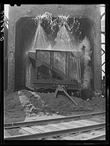 A black and white photo of an industrial-sized container of hot ashes being soaked by water from spigots above