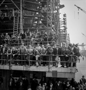 A 1943 photograph shows workers gathered to hear a speech.