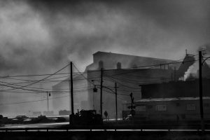 A black and white photograph showing smoke around the mill buildings