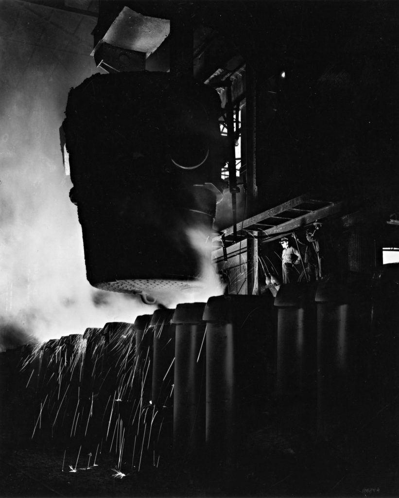 A black and white photo shows a worker standing next to an en enormous ladle of molten metal