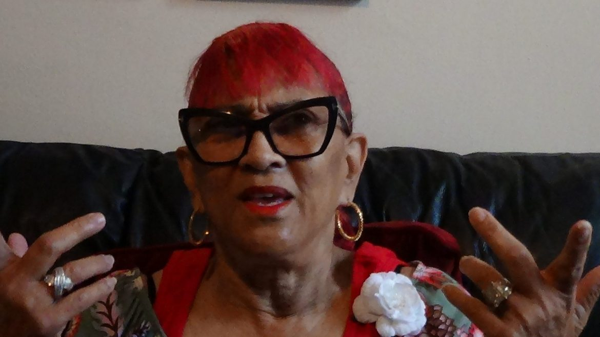 A woman with dyed red hair speaks and gestures with her hands.