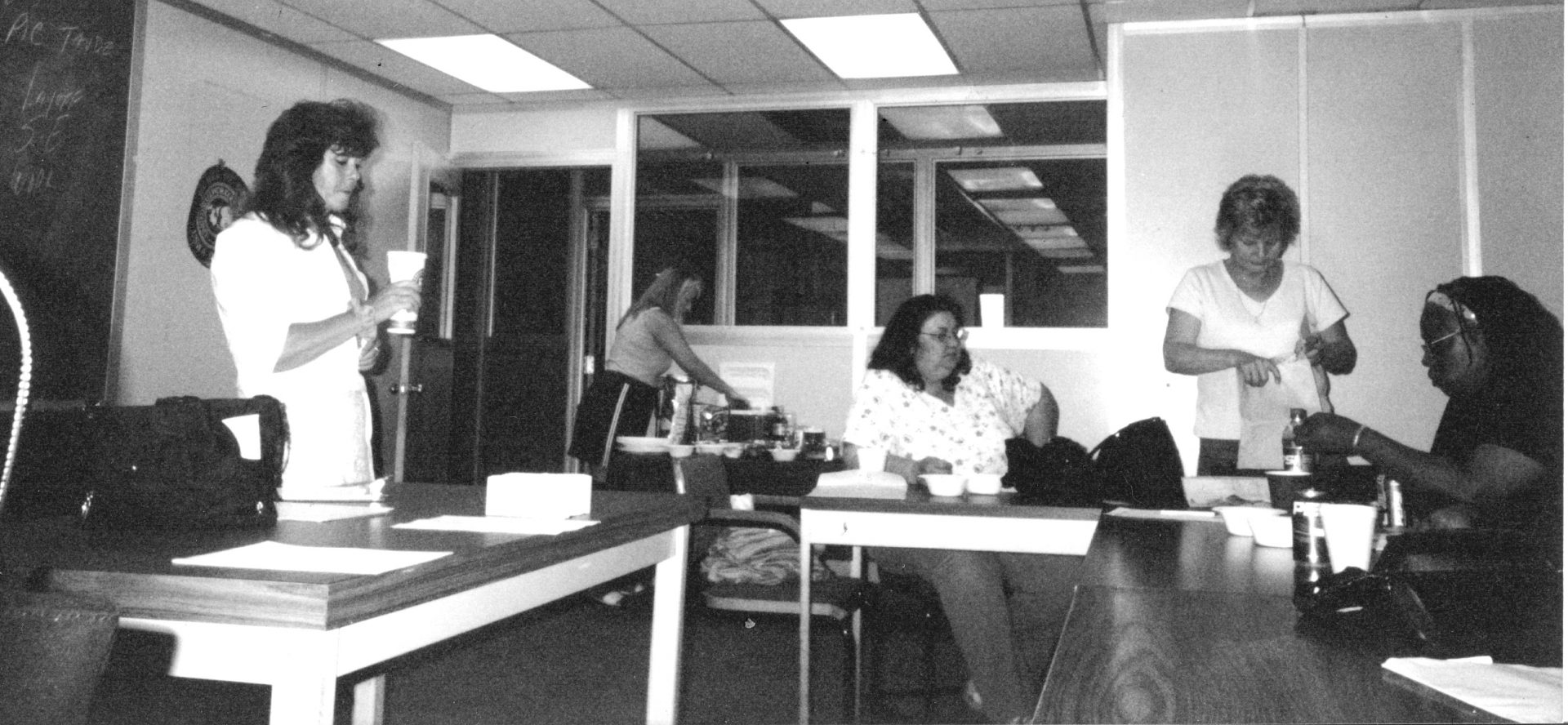 A black and white photo shows five women meeting to discuss union issues.