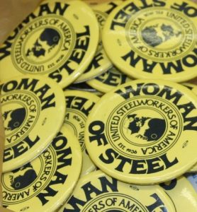 A stack of circular yellow buttons from the United Steelworkers of America's Women of Steel committee.