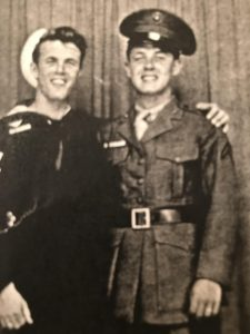 A black-and-white photo shows two brothers, in military uniforms, smiling and embracing.