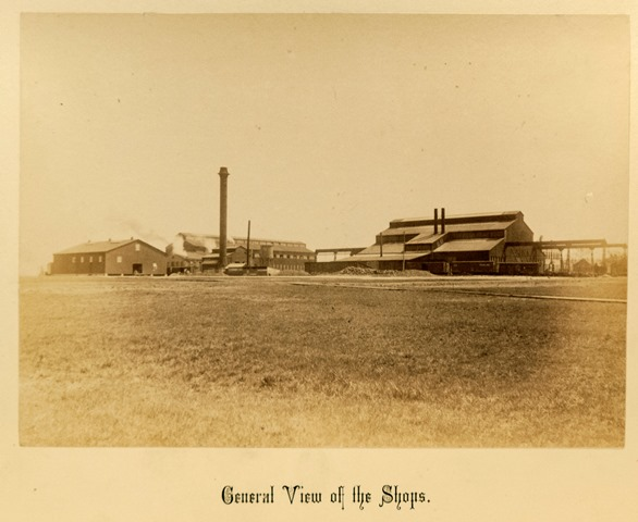 A sepia tone photograph shows a few industrial buildings surrounded by fields
