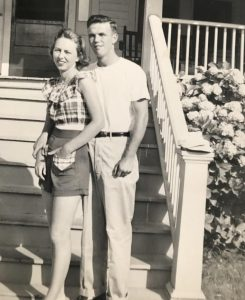 A black-and-white photo shows a young couple outside a suburban house in the 1950s