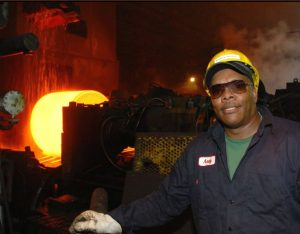 A color photograph shows molten, liquid steel being shaped in heavy machinery with a Black worker wearing a jumpsuit, helmet, gloves, and goggles.