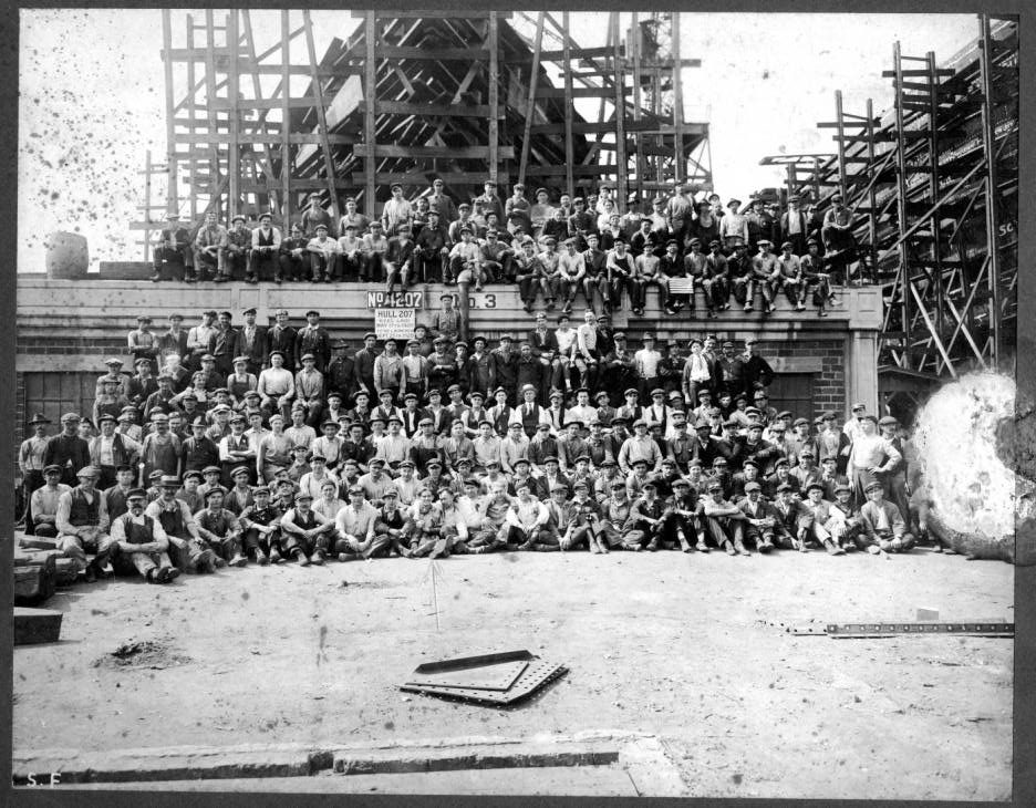 A black & white photo shows a large group of shipyard workers, most of whom are white men, posing in front of a building with scaffolding.