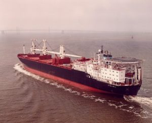 A color photograph shows a large container ship on the water