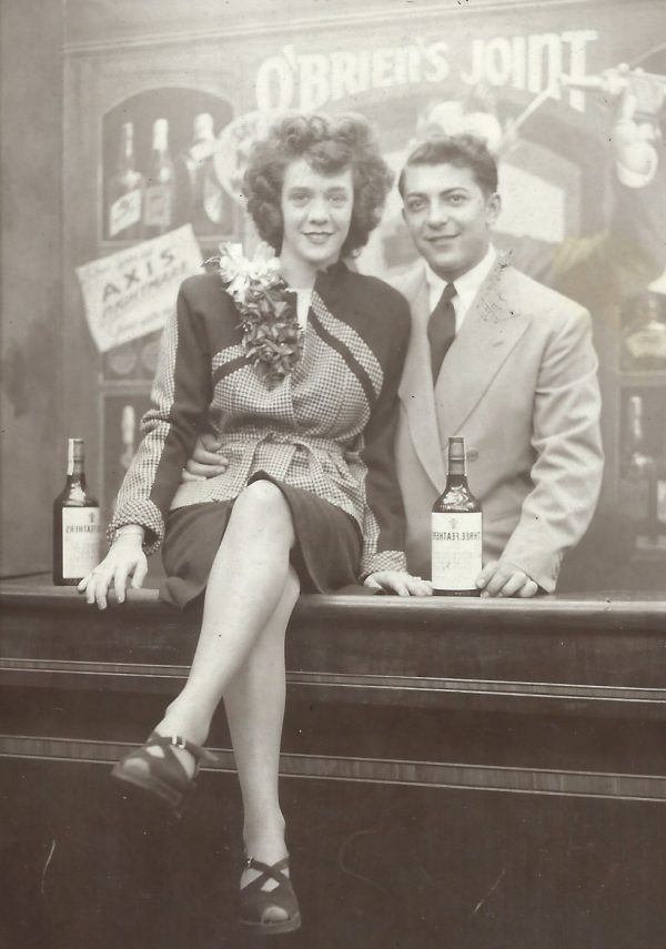 A black and white photograph shows a young woman sitting on a bar counter next to a young man in a suit.