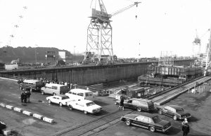 A black and white photo shows the building basin at the Sparrows Point shipyard, with a large crane overhead