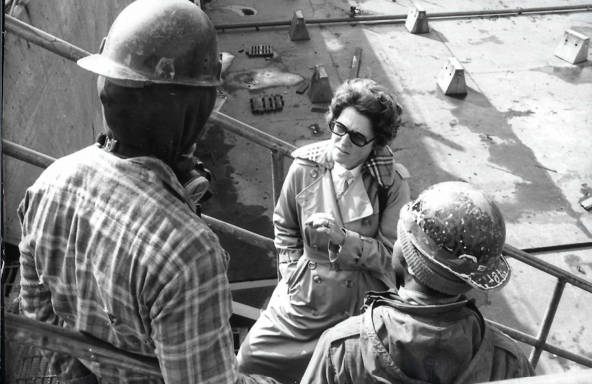 A black and white photo from 1982 shows a woman meeting with two shipyard workers on an exterior staircase
