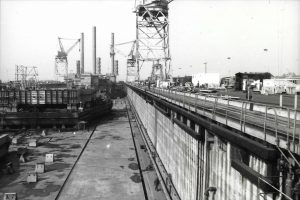A black and white photo shows oil rigs under construction at the shipyard's building basin