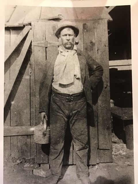 Black and white photograph from the 1800s showing steelworker with lunch pail