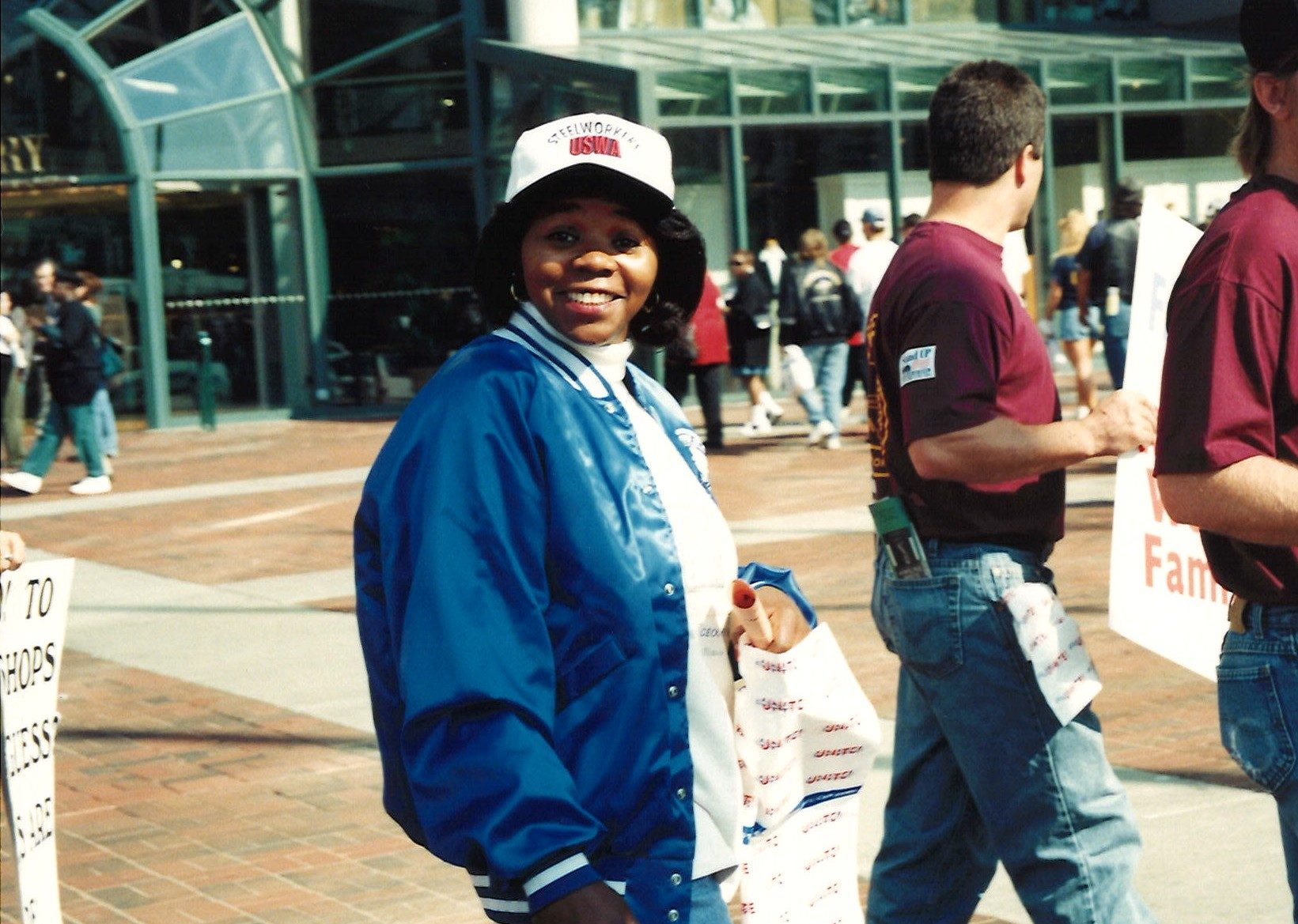 Color photo of Black woman in a blue jacket and a baseball cap.