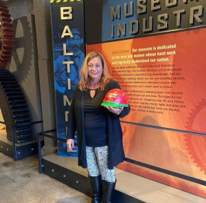 A woman stands in the BMI's lobby holding a red and green hard hat.