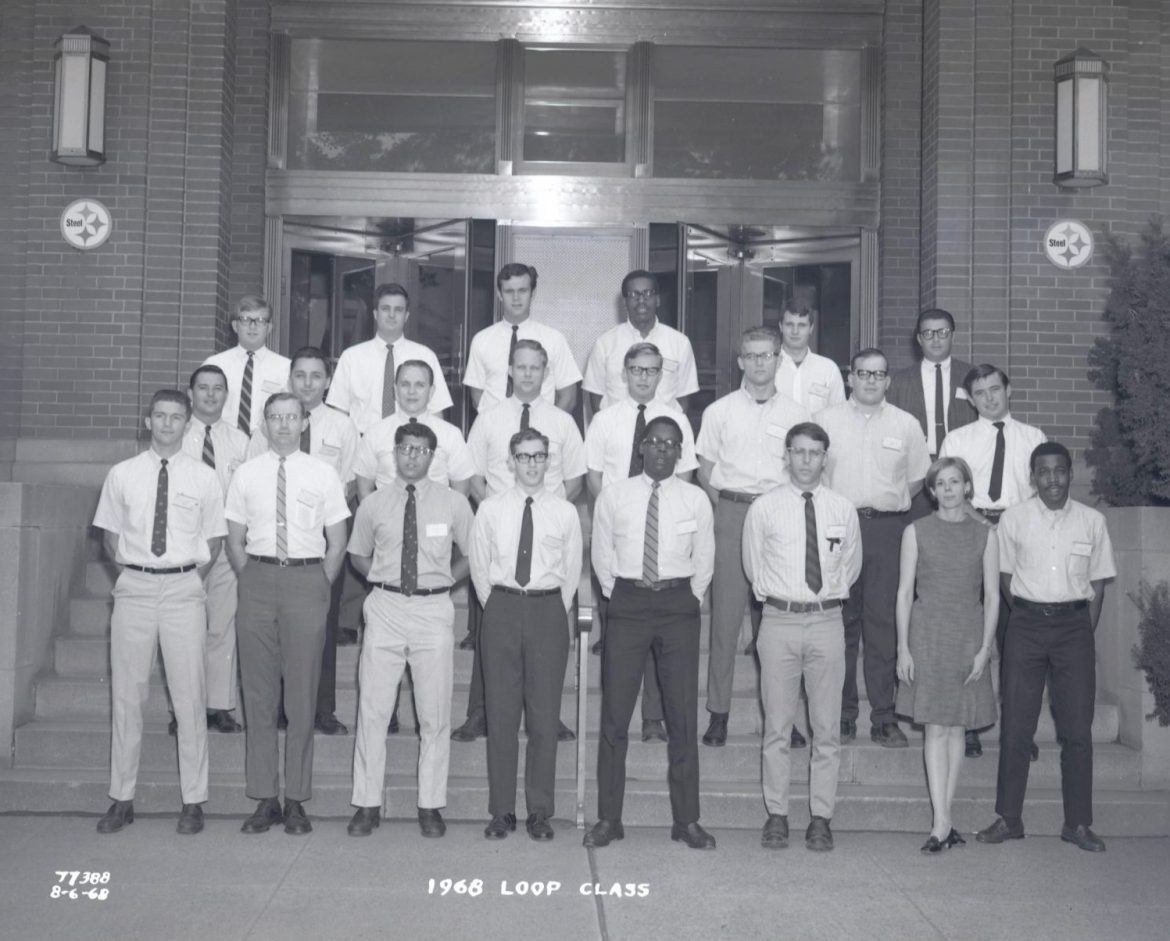 A black and white photo shows a group of young engineers wearing slacks and button-up shirts, standing on steps