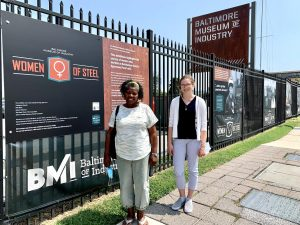 Two women stand beside an outdoor exhibition along the museum's Key Highway fence