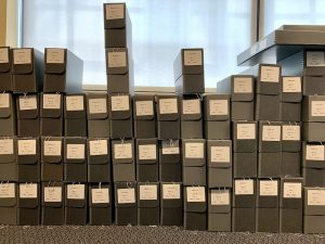 """About 50 archival """"clamshell"""" boxes, labeled and arranged in three tidy stacks, at the BMI's archives"""