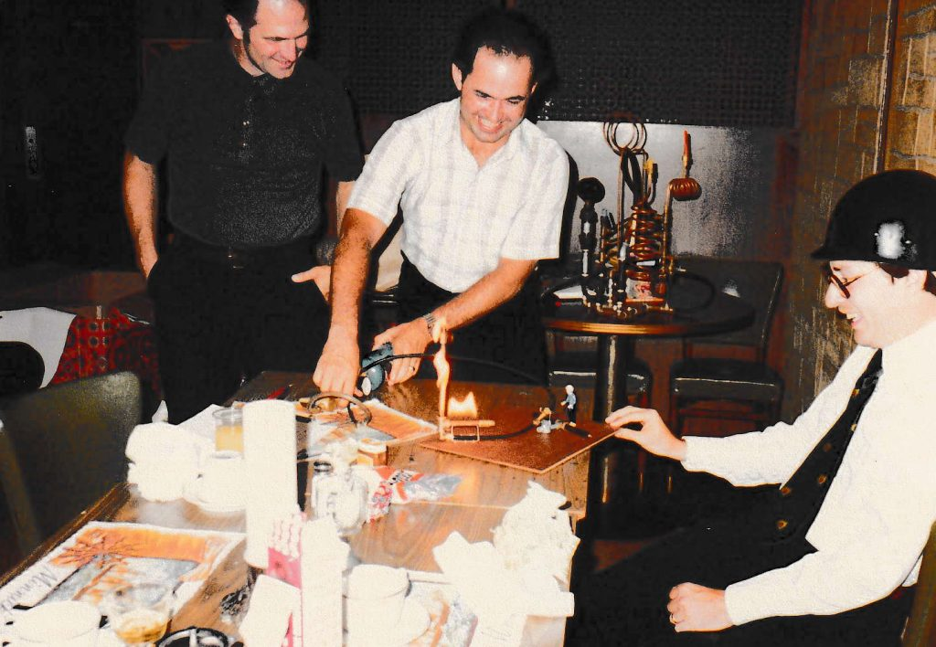 A color photo shows three men smiling and looking at a small, working model of the L blast furnace on a table with food and drinks